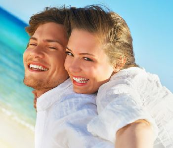 man and woman smiling with beautiful teeth